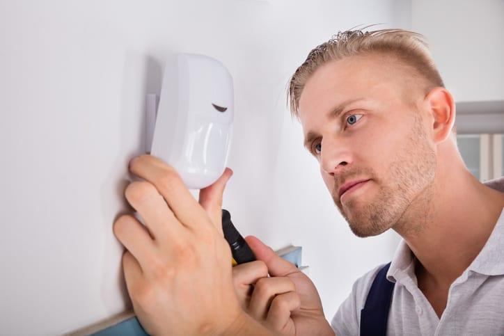Man installing motion sensor for security system.